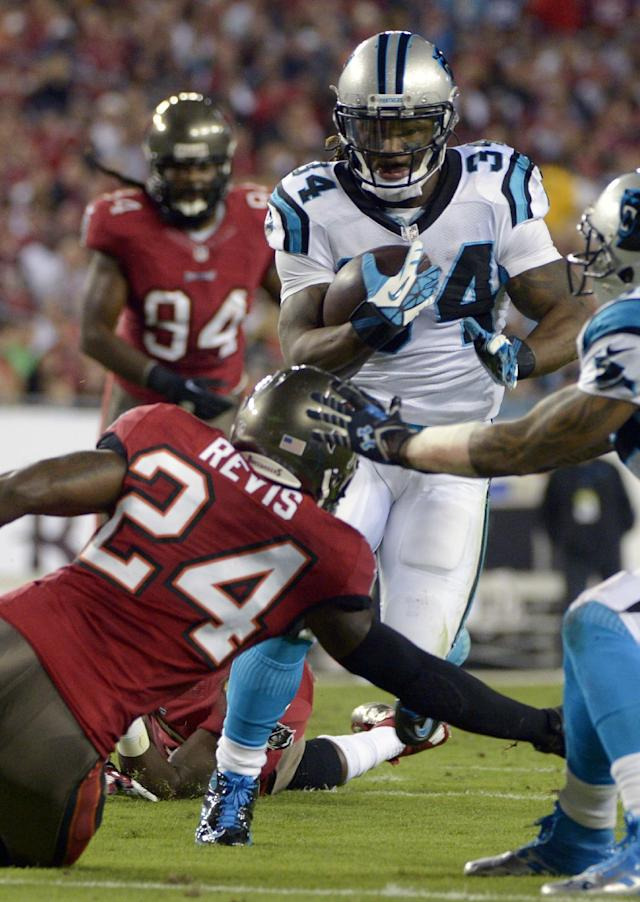 Carolina Panthers running back DeAngelo Williams (34) gets past Tampa Bay Buccaneers cornerback Darrelle Revis (24) for a 12-yard touchdown run during the first half of an NFL football game in Tampa, Fla., Thursday, Oct. 24, 2013. (AP Photo/Phelan M. Ebenhack)