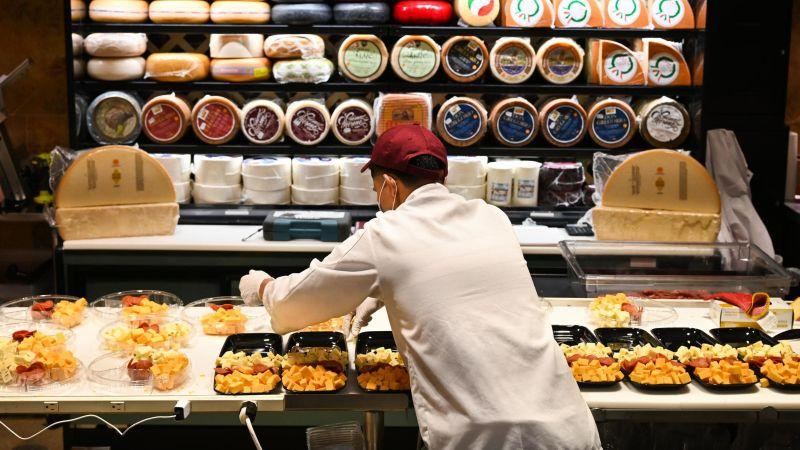 grocery store worker arranges cheese