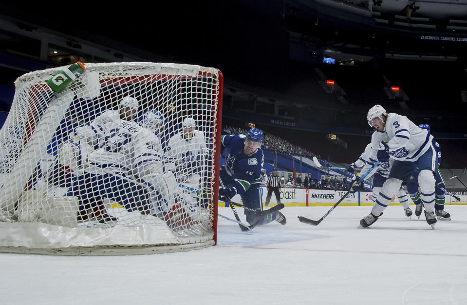 Vancouver Canucks' Tanner Pearson, center, scores against Toronto Maple Leafs goalie David Rittich as Justin Holl (3) watches during the third period of an NHL hockey game Tuesday, April 20, 2021, in Vancouver, British Columbia. (Darryl Dyck/The Canadian Press via AP)