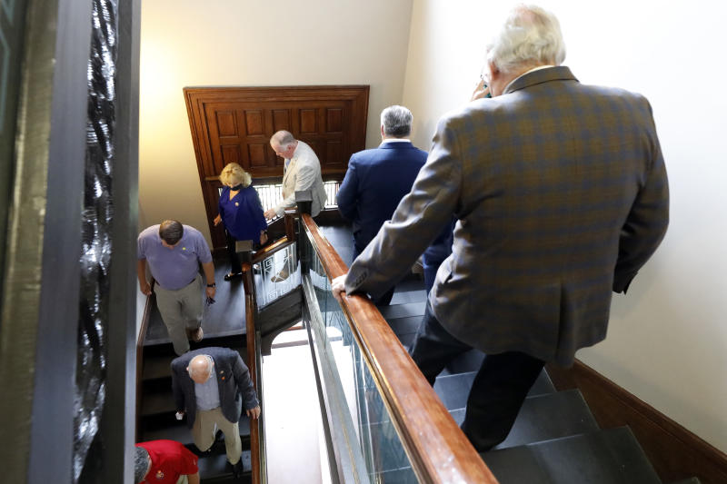 FILE - In this June 27, 2020, file photo, Republican members of the House walk to the Ways and Means conference room to caucus, at the Capitol in Jackson, Miss. Mississippi is seeing the largest outbreak of COVID-19 among legislators in any state.  (AP Photo/Rogelio V. Solis, File)