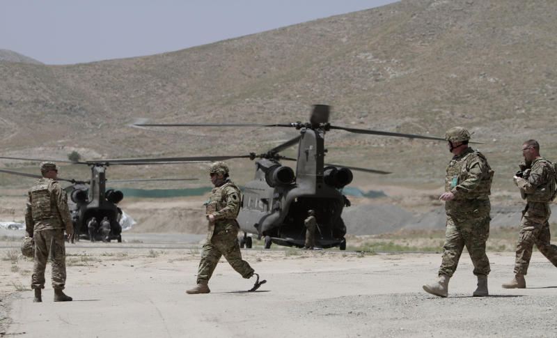 NATO solders move towards helicopters after a ceremony at a military academy on the outskirts of Kabul, Afghanistan, Tuesday, June 18, 2013. Afghan forces have taken over the lead from the U.S.-led NATO coalition for security nationwide, Afghanistan President Hamid Karzai announced in the significant milestone in the 12-year war. (AP Photo/Rahmat Gul)