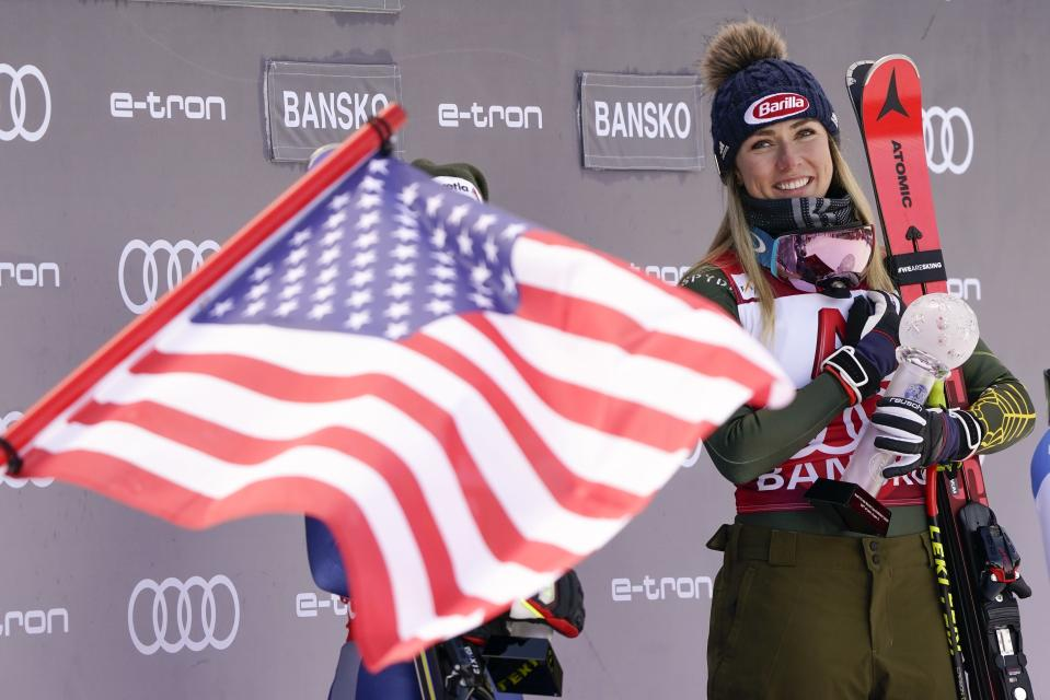 United States' Mikaela Shiffrin is fried by a US flag as she smiles on the podium after winning an alpine ski, women's World Cup super-G, in Bansko, Bulgaria, Sunday, Jan. 26, 2020. (AP Photo/Giovanni Auletta)