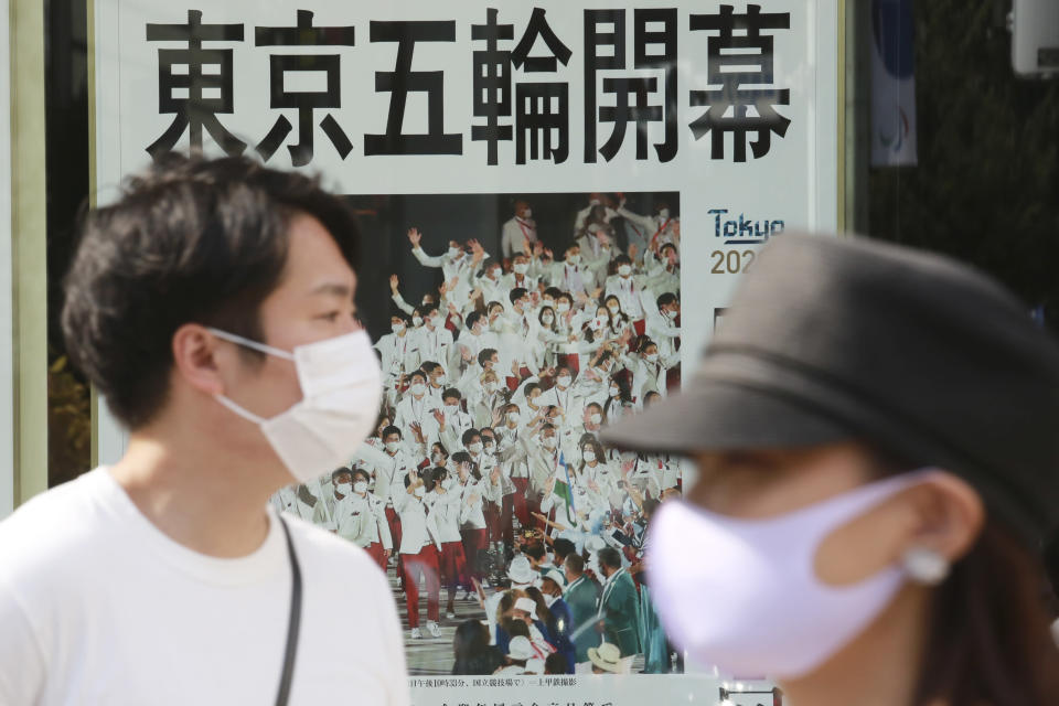 People wearing face masks to protect against the spread of the coronavirus walk past an extra paper reporting Tokyo Olympics start in Tokyo Saturday, July 24, 2021. (AP Photo/Koji Sasahara)