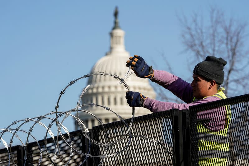 FILE PHOTO: Workers remove razor wire from security fencing near the U.S. Capitol in Washington
