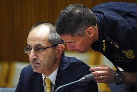 Michael Pezzullo, Secretary of the department of immigration and border protection, is spoken to by a department officer during his appearance at an Australian Senate Estimates Committee in Parliament House, Canberra