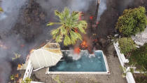 Hot lava reaches a swimming pool after an eruption of a volcano on the island of La Palma in the Canaries, Spain, Monday, Sept. 20, 2021. Giant rivers of lava are tumbling slowly but relentlessly toward the sea after a volcano erupted on a Spanish island off northwest Africa. The lava is destroying everything in its path but prompt evacuations helped avoid casualties after Sunday's eruption. (Europa Press via AP)
