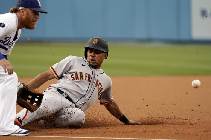 San Francisco Giants' LaMonte Wade Jr., right, steals third base next to Los Angeles Dodgers third baseman Justin Turner during the first inning of a baseball game Thursday, July 22, 2021, in Los Angeles. (AP Photo/Marcio Jose Sanchez)