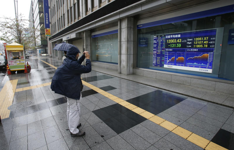 A man takes a picture of an electronic stock indicator in Tokyo, Japan, Tuesday, April 2, 2013. A slowdown in U.S. factory production sent Asian stock markets lower Tuesday, while Japan's Nikkei slipped as the yen rose against the dollar. (AP Photo/Shizuo Kambayashi)