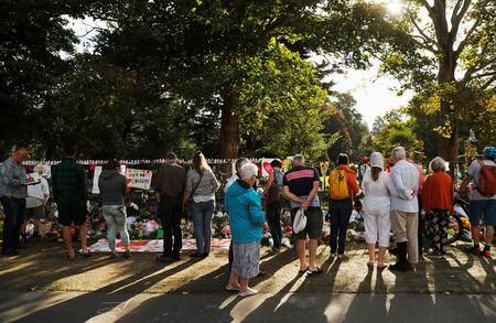 People visit a memorial site for victims of Friday's shooting, in front of Christchurch Botanic Gardens in Christchurch