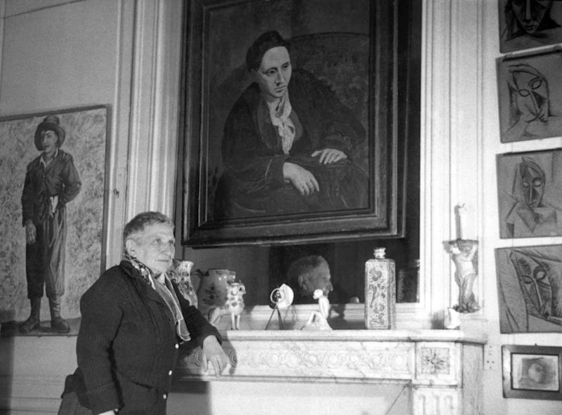 American writer Gertrude Stein (1874-1946), posing with a portrait of herself painted by Picasso in 1906