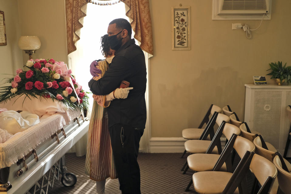"""FILE - In this May 2, 2020, file photo, siblings Erika and Dwayne Bermudez comfort one another during a short viewing of their mother, Eudiana Smith, who died of coronavirus, at The Family Funeral Home in Newark, N.J. """"I was robbed of the experience of being able to celebrate her life in a manner that would offer some kind of respect for the woman she was,"""" Erika Bermudez said. She did her best, live-streaming the ceremony to friends and family who couldn't attend. (AP Photo/Seth Wenig)"""