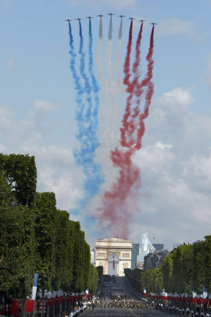 French aircraft trail smoke in the colours of France's tricolour over the Arc de Triomphe and the the Champs Elysees at the start of the traditional Bastille Day parade in Paris, Thursday July 14, 2011. (AP Photo/Remy de la Mauviniere)