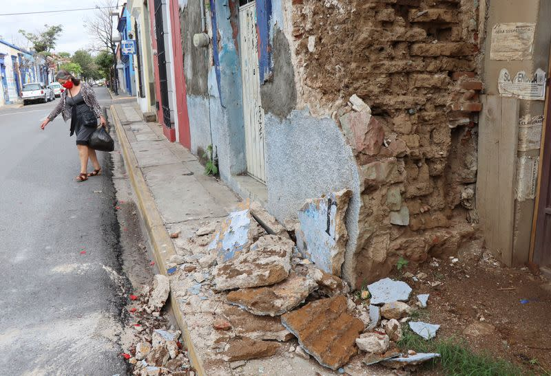 A woman walks by a building damaged during a quake, in Oaxaca