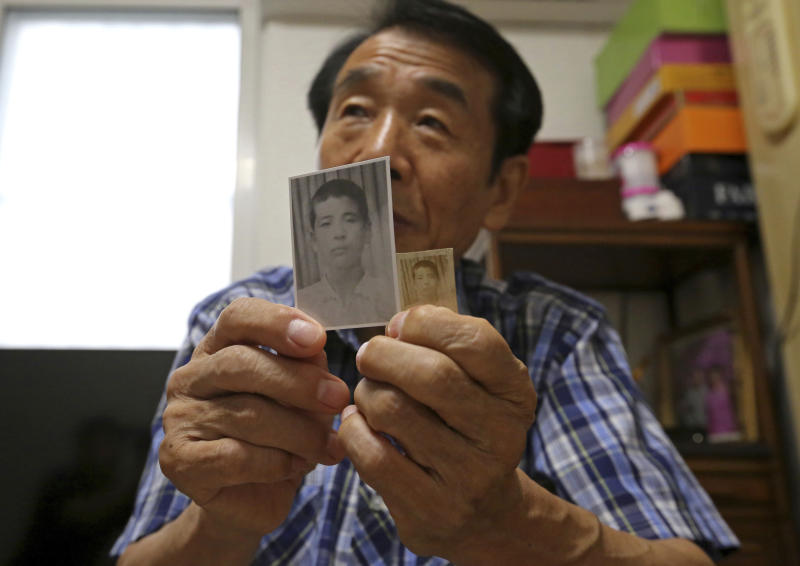 In this Aug. 17, 2018, photo, Lee Soo-nam, 76, shows photos of his brother Ri Jong Song in North Korea during an interview at his home in Seoul, South Korea. Lee is among about 200 war-separated South Koreans and their family members who are crossing into North Korea for heart-wrenching meetings with relatives they haven't seen for decades. The week-long event beginning Monday, Aug. 20, 2018, at North Korea's Diamond Mountain resort come as the rival Koreas boost reconciliation efforts amid a diplomatic push to resolve the North Korean nuclear crisis. (AP Photo/Ahn Young-joon)