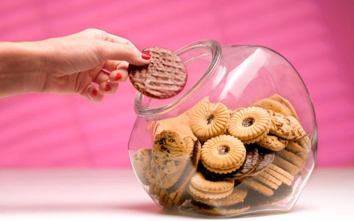 Woman sneaks a biscuit treat from the cookie jar - Peter Dazeley/The Image Bank RF