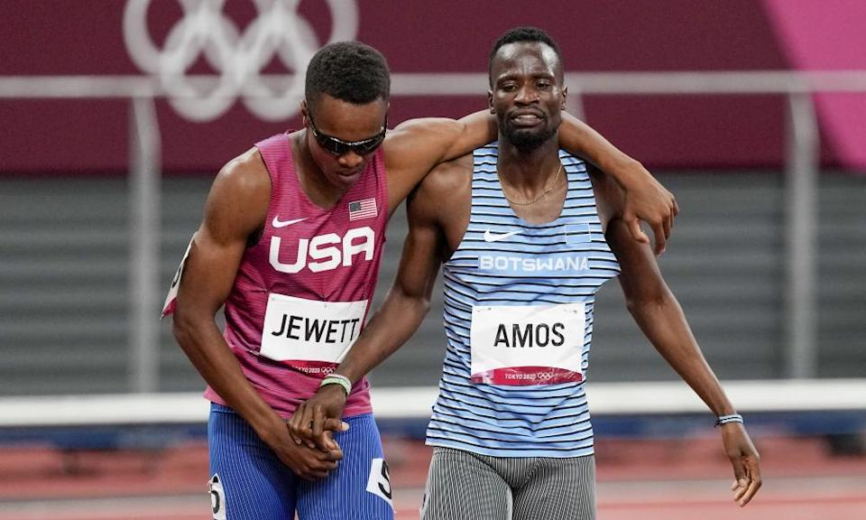 Isaiah Jewett, of the United States, and Nijel Amos, right, of Botswana, shake hands after falling in the men's 800m semi-final.