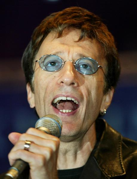 FILE This Saturday, Sept. 25, 2004, file photo shows former Bee Gees singer Robin Gibb, performing a song at the beginning of a show match between former German tennis star Steffi Graf and Argentina's Gabriela Sabatini at the Max-Schmeling-Halle hall on in Berlin. British media reports said Saturday April 14, 2012 former Bee Gee Robin Gibb is gravely ill with pneumonia in a London hospital. The Sun newspaper reported Saturday that 62-year-old Gibb is in a coma, citing a family friend.(AP Photo/ Jan Bauer)