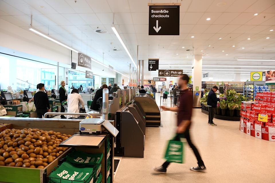 A man walks towards a Woolworths checkout.