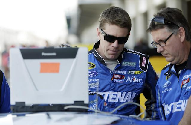 Driver Carl Edwards, left, talks with a crew member before practice for the Brickyard 400 Sprint Cup series auto race at the Indianapolis Motor Speedway in Indianapolis, Friday, July 25, 2014. (AP Photo/AJ Mast)
