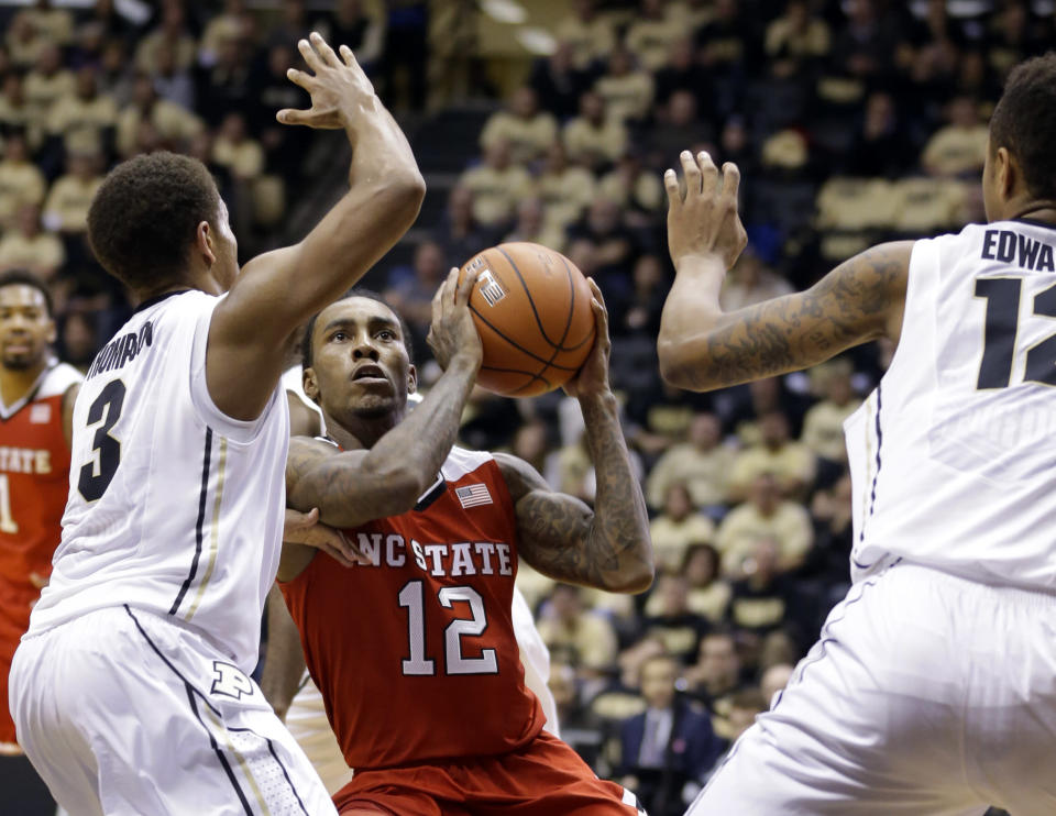 North Carolina State guard Anthony Barber, center looks to shoots between Purdue guard P.J. Thompson, left, and forward Vince Edwards in the first half of an NCAA college basketball game in West Lafayette, Ind., Tuesday, Dec. 2, 2014. (AP Photo/Michael Conroy)