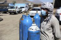 A man waits inside a privately owned oxygen factory to get his oxygen cylinders refilled, in Kabul, Afghanistan, Saturday, June 19, 2021. Health officials say Afghanistan is fast running out of oxygen as a deadly third surge of COVID worsen. (AP Photo/Rahmat Gul)