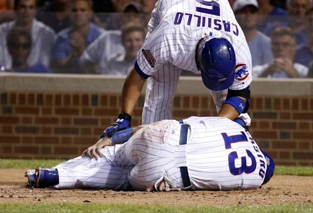 Chicago Cubs' Welington Castillo looks over Starlin Castro, bottom, after Castro injured himself after sliding safely into home plate, scoring on a single by Jorge Soler, during the first inning of a baseball game against the Milwaukee Brewers, Tuesday, Sept. 2, 2014, in Chicago. (AP Photo/Charles Rex Arbogast)