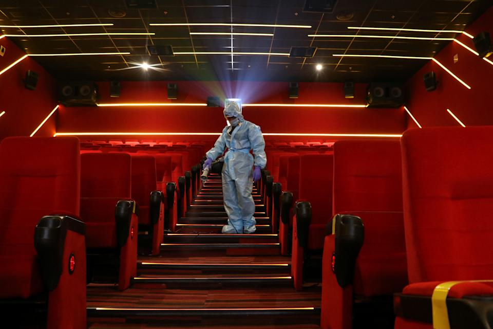 A worker wearing personal protective equipment (PPE) sanitizes seats inside the Inox Leisure movie theatre ahead of its reopening, amidst the outbreak of the coronavirus disease (COVID-19), in Mumbai, India, October 13, 2020. REUTERS/Niharika Kulkarni