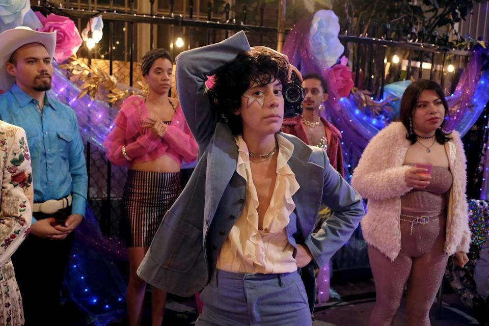 """Actor Roberta Colindrez is shown in a blue suit in a party setting on the set of the TV show """"Vida"""""""