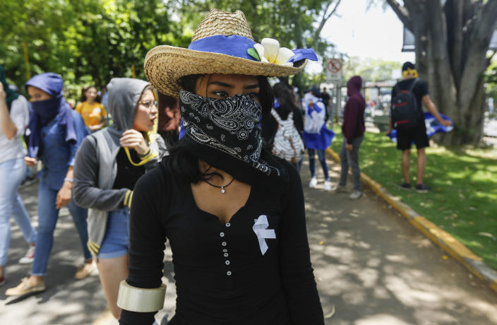 A student hiding her identify for fear of being identified and later attacked by security forces or government supporters attends a protest demanding the release of all political prisoners, on the last day of a 90-day period for releasing such prisoners as agreed to during negotiations between the government and opposition, on the Central American University (UCA) campus where security forces legally cannot enter in Managua, Nicaragua, Tuesday, June 18, 2019. Nicaragua's government said Tuesday that it has released all prisoners detained in relation to 2018 anti-government protests, though the opposition maintains that more than 80 people it considers political prisoners are still in custody. (AP Photo/Alfredo Zuniga)