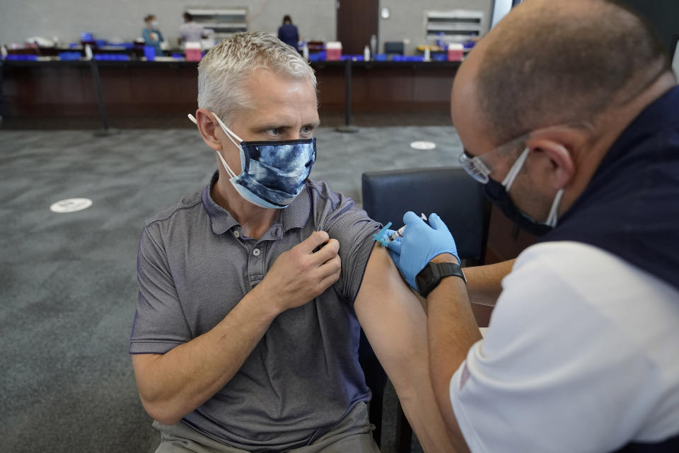 Paul Clasby, of Holliston, Mass., left, receives his second shot of Moderna COVID-19 vaccine from paramedic Jake Lees, of North Attleborough, Mass., right, at a mass vaccination clinic, Wednesday, May 19, 2021, at Gillette Stadium, in Foxborough, Mass. A month after every adult in the U.S. became eligible for the vaccine, a distinct geographic pattern has emerged: The highest vaccination rates are concentrated in the Northeast, while the lowest ones are mostly in the South. (AP Photo/Steven Senne)