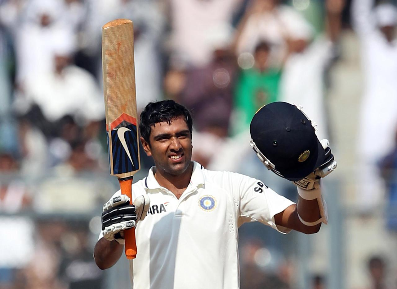Ravichandran Ashwin of India raises his bat and helmet after scoring his first test century during the fourth day of the third test match between India and West Indies at Wankhede stadium on November 25, 2011 in Mumbai, India. (Photo by Santosh Harhare/Hindustan Times via Getty Images).