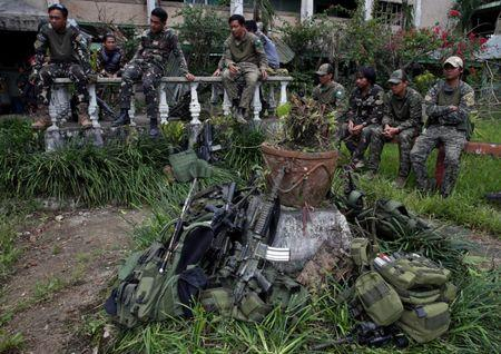 Soldiers take a break inside a compound after government troops cleared the area from pro-Islamic State militant groups inside a war-torn area in Bangolo town, Marawi City, southern Philippines October 23, 2017. REUTERS/Romeo Ranoco