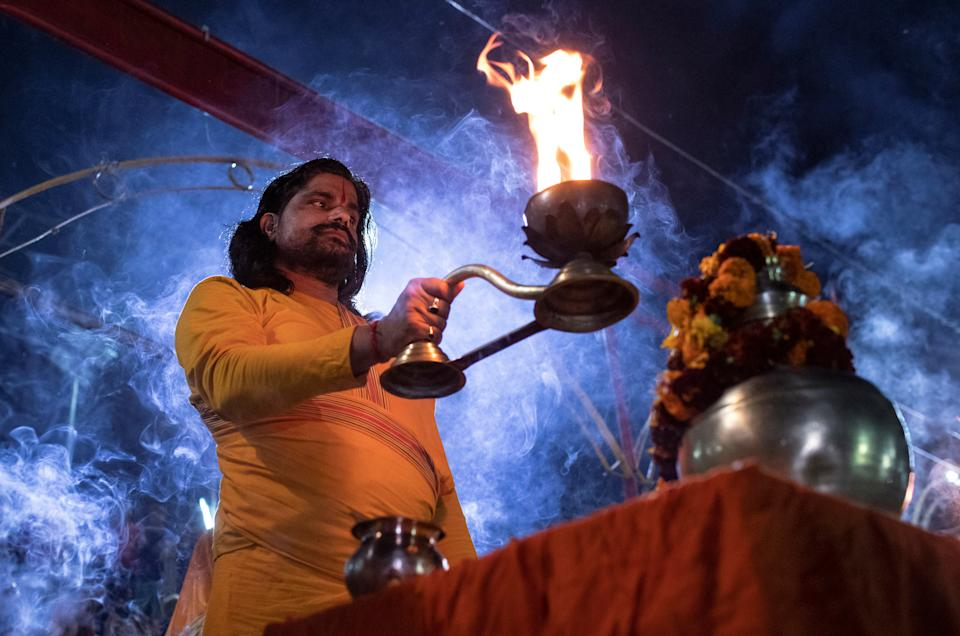 A Hindu priest holds an oil lamp during evening prayers on the banks of Sarayu river after Supreme Court's verdict on a disputed religious site, in Ayodhya, India, November 9, 2019. REUTERS/Danish Siddiqui