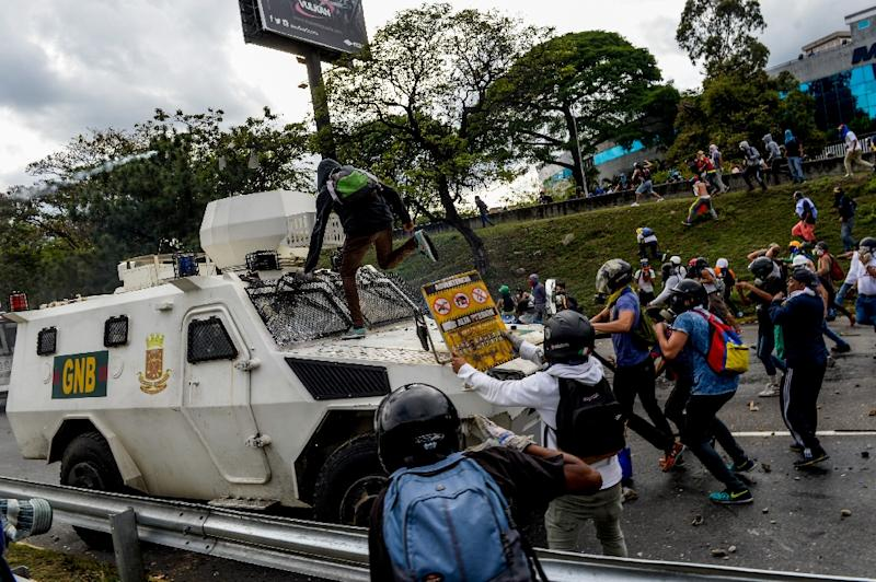 Venezuelan opposition activists confront a police armoured vehicle during a protest against President Nicolas Maduro, in Caracas, on May 1, 2017 (AFP Photo/Federico Parra)