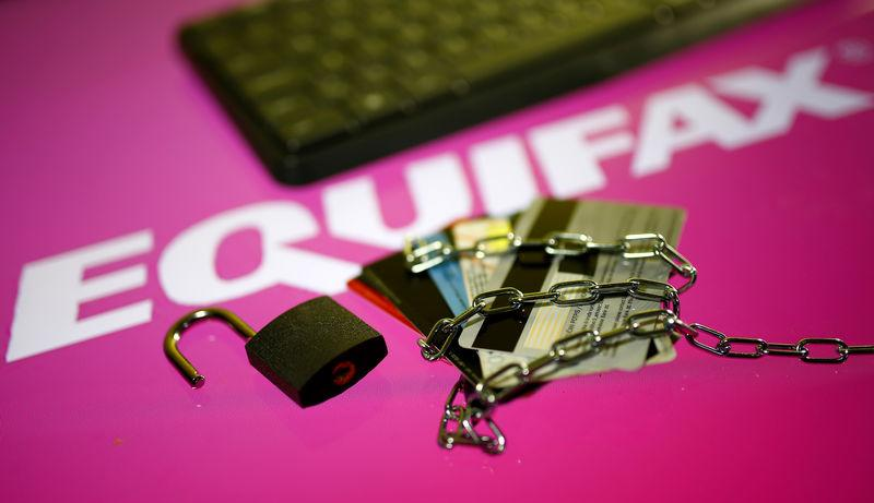 Credit cards, a chain and an open padlock is seen in front of displayed Equifax logo in this illustration