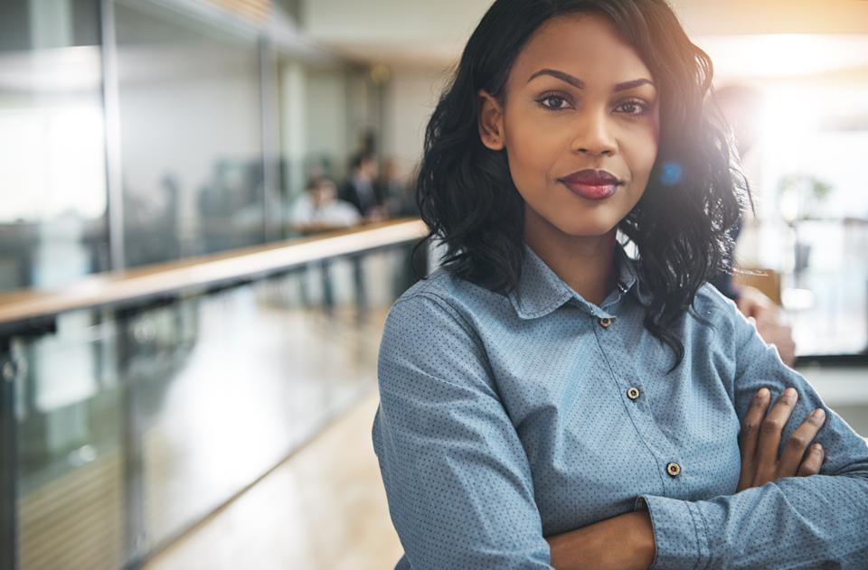Pretty young dreamy African-American office worker standing with arms crossed and looking at camera.