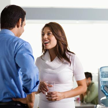 Young-man-talking-to-female-colleague-by-watercooler_web