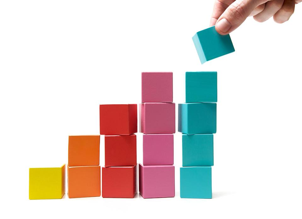 Putting the final building block onto the top of a rising pile signifying success and achievement