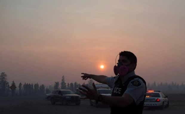 An RCMP officer is surrounded by smoke and silhouetted by the setting sun about 16 kilometres south of Fort McMurray on May 6, 2016.