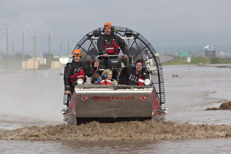 A search and rescue boat carries rescued passengers from a flooded industrial site near highway 543 north of High River, Alberta, Canada on Friday, June 21, 2013. The rescued passengers spent the night moored on a structure they built in the water. Calgary's mayor said Friday the flooding situation in his city is as under control as it can be, for now. Officials estimated 75,000 people have been displaced in the western Canadian city. Mayor Naheed Nenshi said the Elbow River, one of two rivers that flow through the southern Alberta city, has peaked. (AP Photo/The Canadian Press, Jordan Verlage)