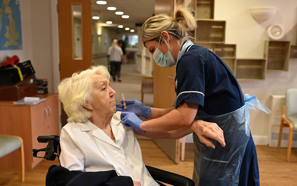 Practice Nurse Victoria Parkinson gives a dose of the Oxford-AstraZeneca Covid-19 vaccine to resident Ann Wilkinson, 94, at the Belong Wigan care home in Wigan, northwest England - OLI SCARFF/AFP