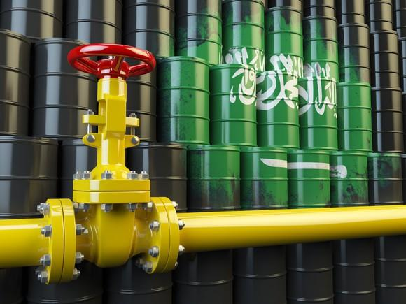Oil-pipeline valve in front of barrels painted like the Saudi flag