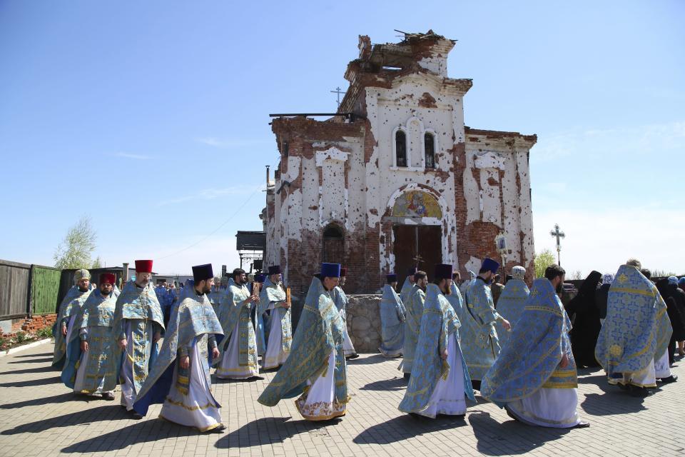 Priests attend a religion procession celebrating Orthodox Easter at the Iversky Monastery a monastery of the Ukrainian Orthodox Church (Moscow Patriarchate) damaged by shelling, outside Donetsk, Ukraine, Tuesday, May 4, 2021. (AP Photo/Alexei Alexandrov)