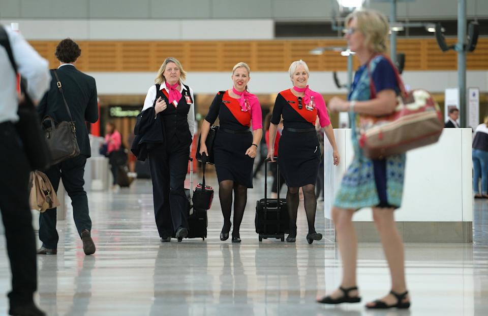 Qantas staff (C) walk through the terminal of Sydney domestic airport on 27 February, 2014. Struggling Australian carrier Qantas February 27 said it will axe 5,000 jobs, defer aircraft deliveries and freeze growth at Asian offshoot Jetstar in a major shake-up after deep first-half losses, warning of more pain to come.   AFP PHOTO/William WEST        (Photo credit should read WILLIAM WEST/AFP via Getty Images)