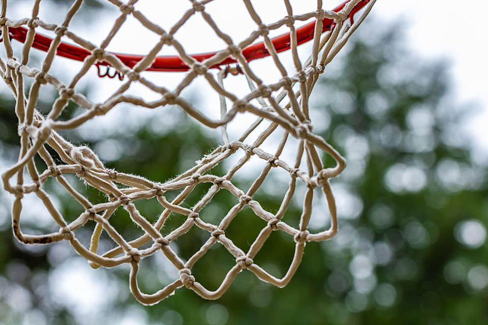 old used basketball hoop with red paint and netting haning in outdoor setting on overcast day