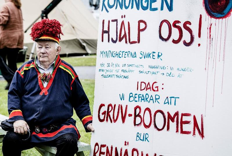 Sami man Josef Pittja, holds a placard appealing for help from the Swedish king, demonstrates outside the Swedish Sami Parliament opening session in Jokkmokk, northern Sweden, on Wednesday Aug. 28, 2013. Swedish King Carl Gustaf attended the Sami Parliament opening session this year as the parliament celebrates its 20th anniversary. Since the end of the last Ice Age, the Sami have wandered the vast landscapes of northern Europe, herding reindeer and nurturing a philosophy of harmony with nature (AP Photo/Carl-Johan Utsi) SWEDEN OUT