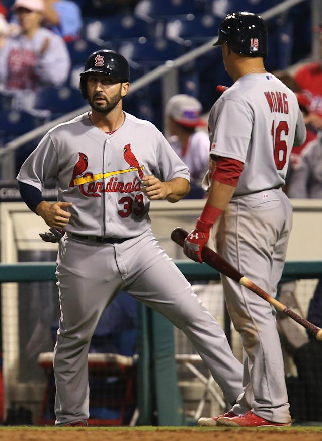 St Louis Cardinals' Daniel Descalso, left, is congratulated by Kolten Wong as he crosses home plate to score on a sacrifice fly by Matt Carpenter in the 12th inning of a baseball game against the Philadelphia Phillies, Saturday, Aug. 23, 2014, in Philadelphia. The Cardinals won 6-5. (AP Photo/Laurence Kesterson)
