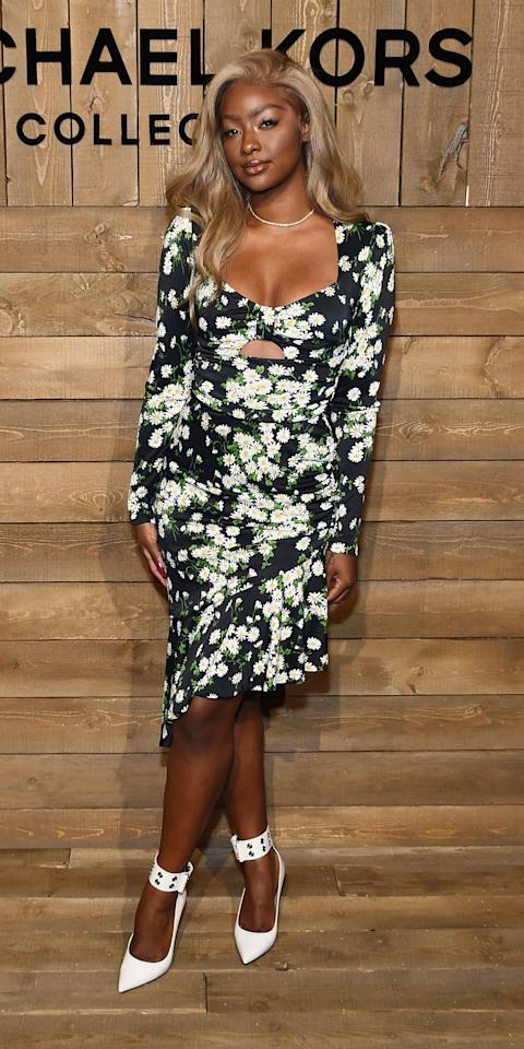 <p>Justine embraced spring style at Michael Kors, wearing a floral cutout dress and white heels with a diamond choker.</p>