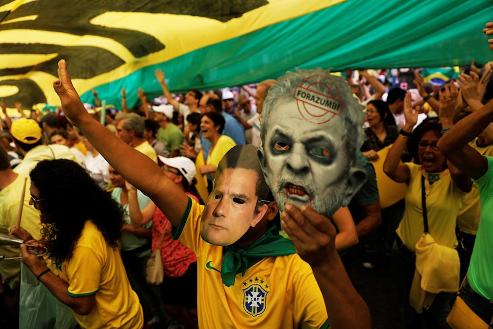 A demonstrator wears a mask of federal judge Sergio Moro as he holds a mask with a defaced picture depicting Brazil's former president Luiz Inacio Lula da Silva in a protest in support of Lava Jato (Car Wash) investigation in Sao Paulo, Brazil, March 26, 2017. REUTERS/Nacho Doce