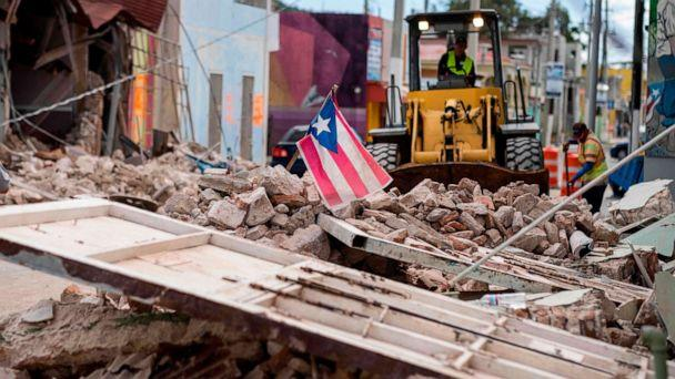 PHOTO: A Puerto Rican flag waves on top of a pile of rubble as debris is removed from a main road in Guanica, Puerto Rico, Jan. 8, 2020, one day after the earthquake. (AFP via Getty Images, FILE)